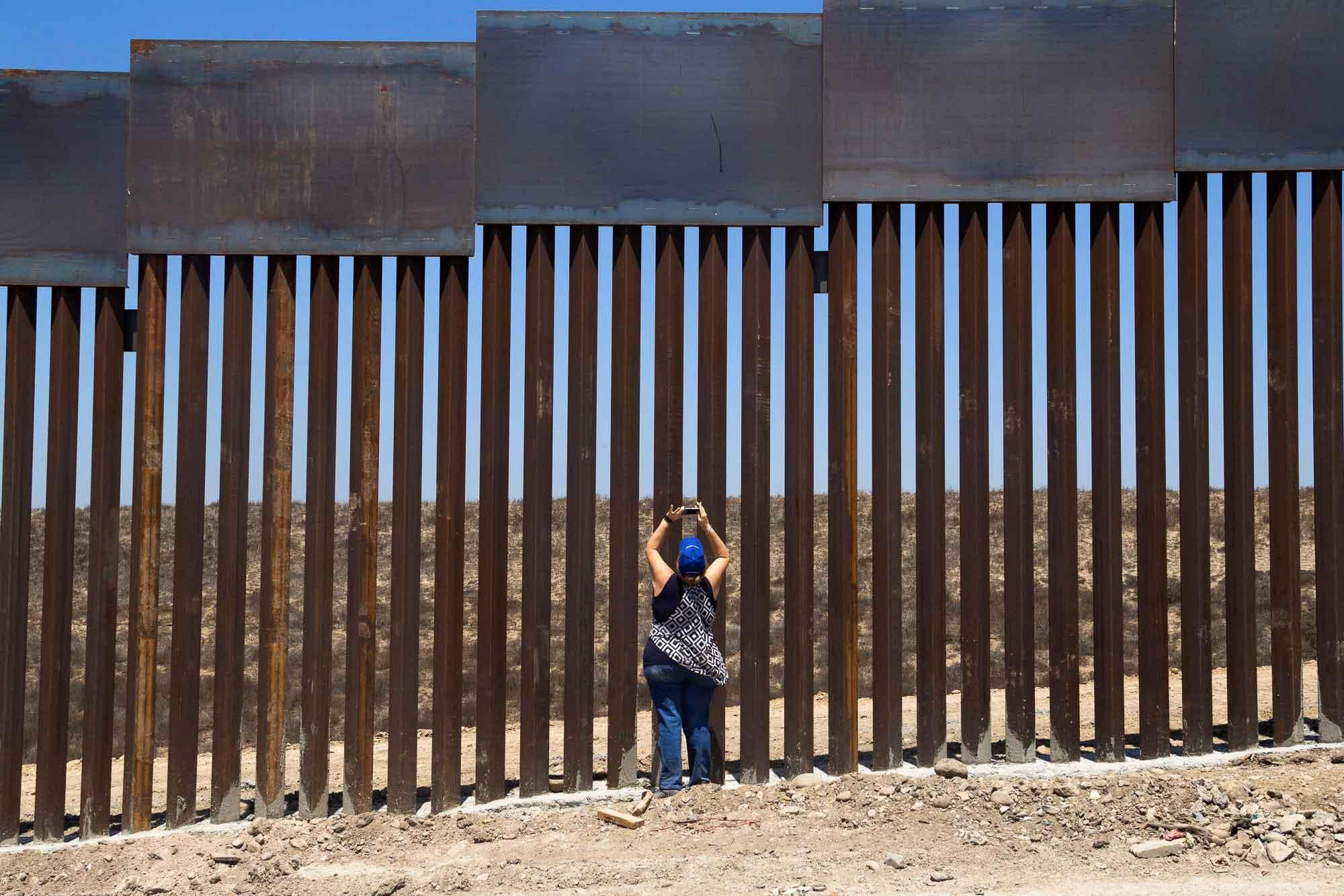 Mujer frente a muro fronterizo