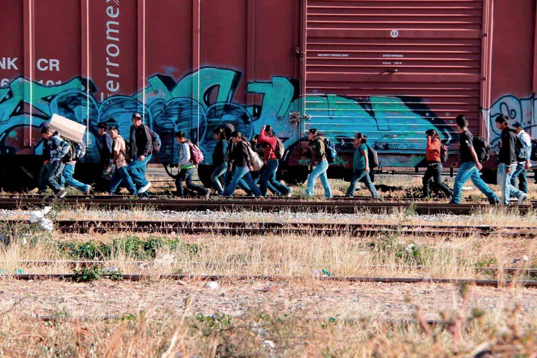 migrantes caminando sobre vias