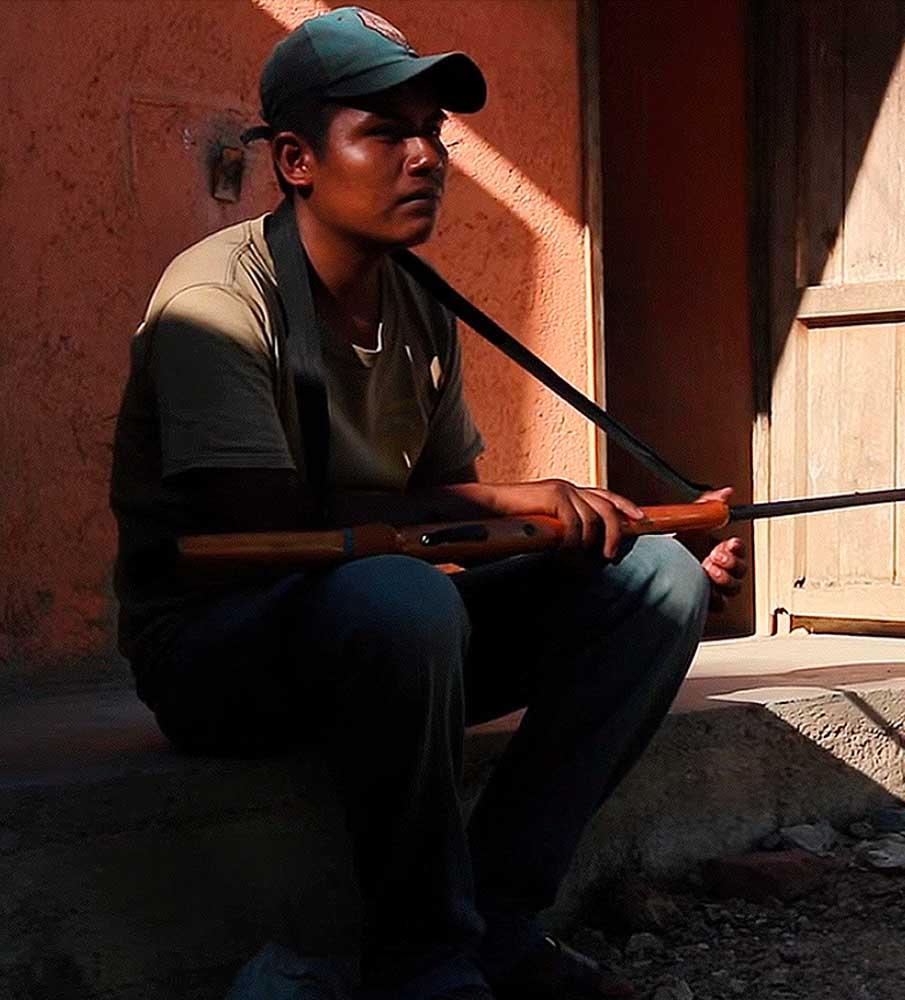 Joven de Guerrero sentado con arma